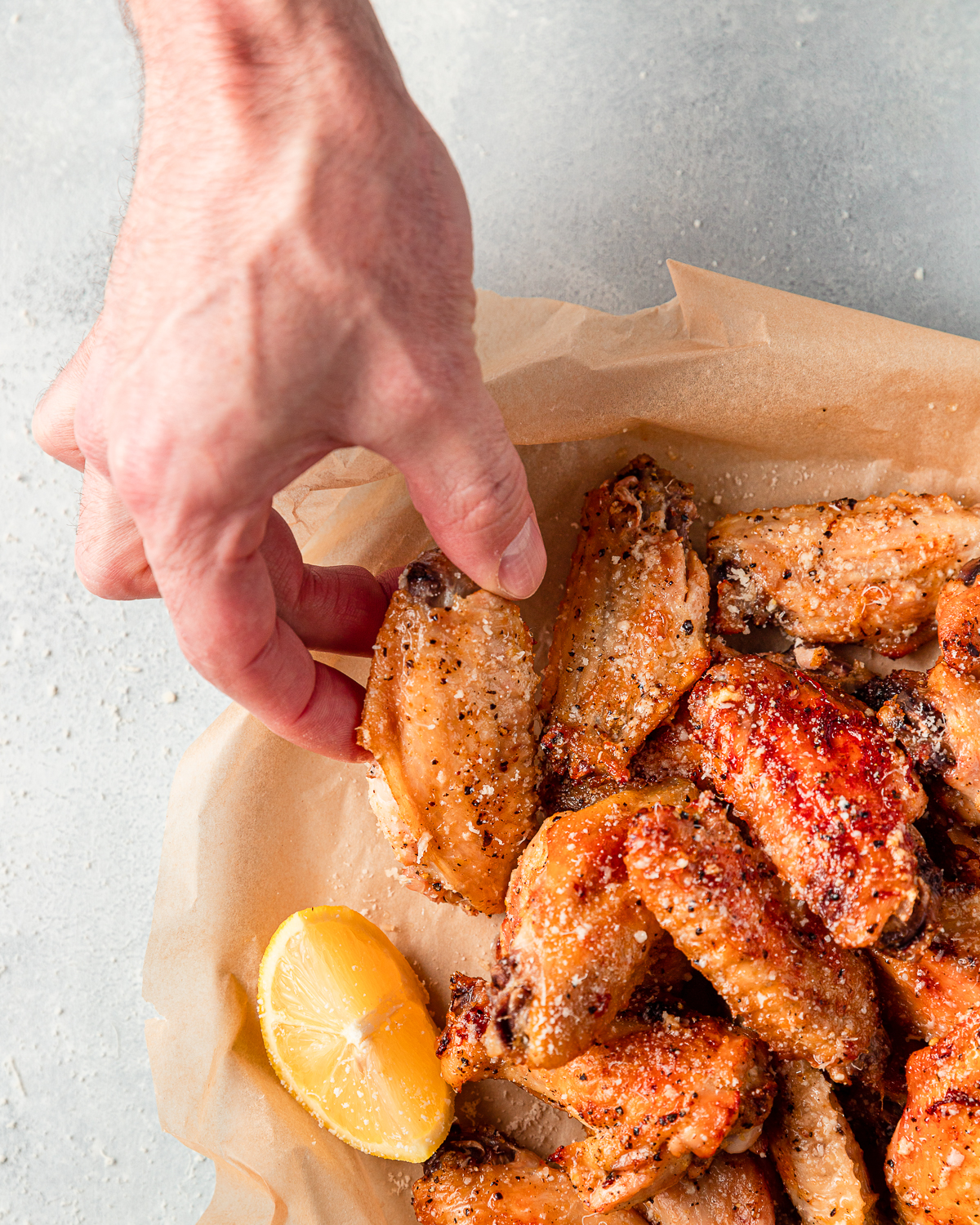A bowl of wings with lemon